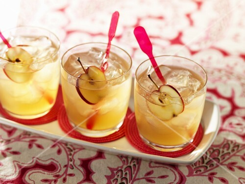 An apple drink (cider and whiskey) with sliced apples and ice cubes