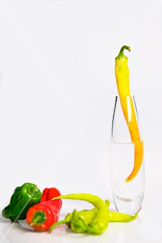 Assorted peppers, one in a glass vase