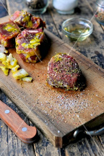 Marinated beef fillets on a wooden board