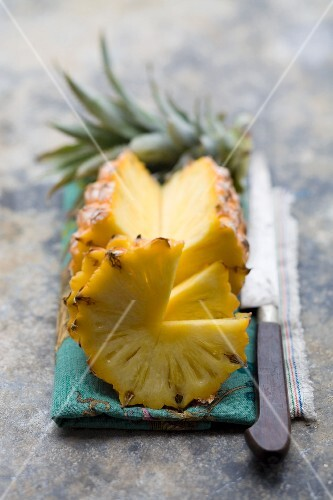 A fresh pineapple, partly sliced