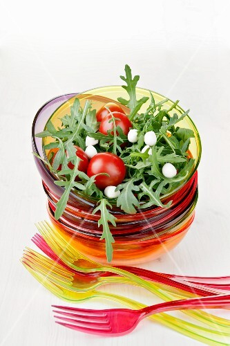Cherry tomatoes on a bed of rocket with mozzarella pearls