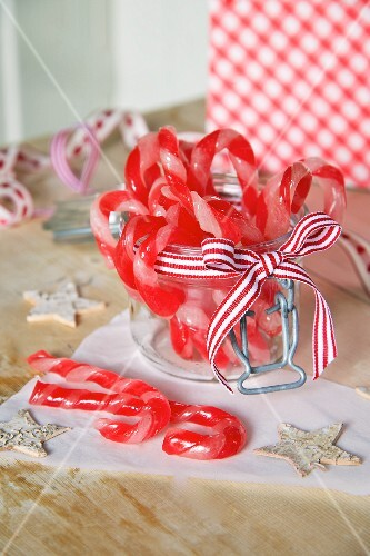 Candy canes in a jar tied with a ribbon for Christmas