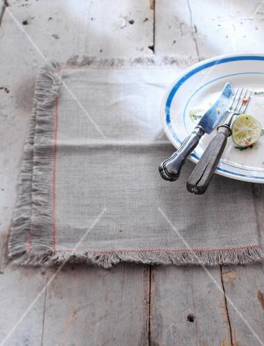 Reste von Salat und Limette auf Teller mit Besteck