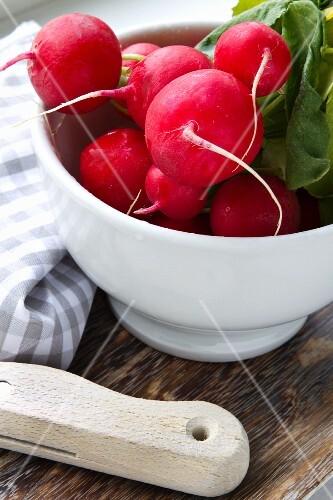 Fresh radishes in a white bowl