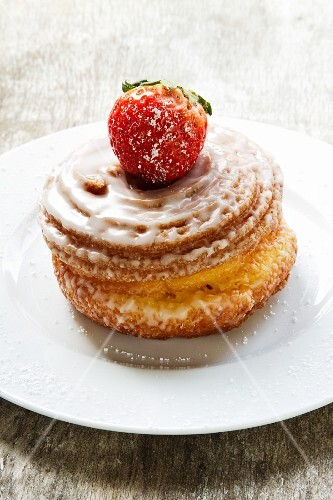 Yeast-raised pastry whirl with sugar glaze and a strawberry