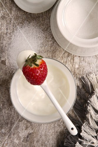 Yoghurt on a spoon with a strawberry; a pot of sugar to one side