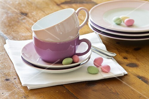 Stacked plates and coffee cups with pastel-coloured sugar eggs
