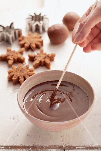 Cake pops being coated with chocolate glaze