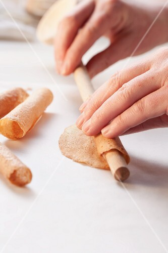 Cigarettes russes being rolled up using a wooden spoon