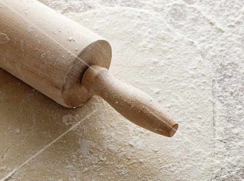 Rolled-out pastry with a rolling pin and flour
