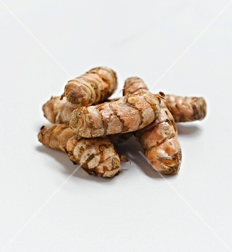 Whole Turmeric Roots on a White Background