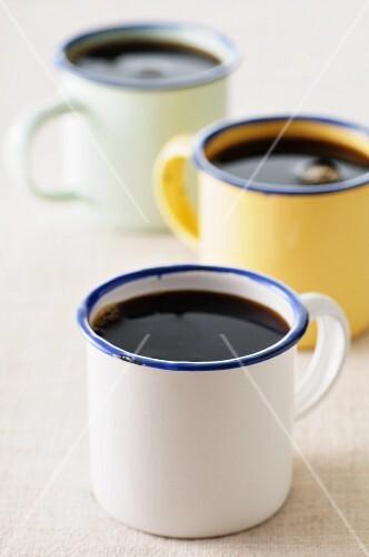 Black coffee in three enamel mugs