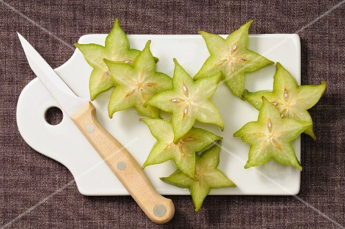 Lots of slices of starfruit on a chopping board