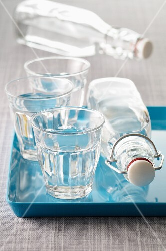 Three glasses of water and two bottles of water, some of these on a blue tray