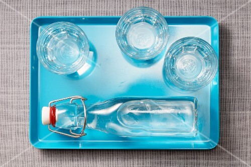 Three glasses of water and a bottle of water on a blue tray