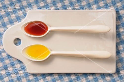 Two spoons with oil and vinegar on a chopping board