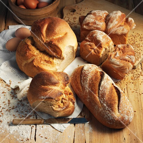 Assorted types of bread on a wooden surface