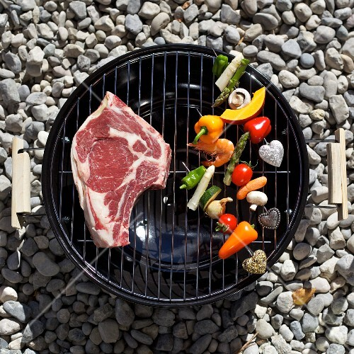 A raw T-bone steak and vegetables on a barbecue