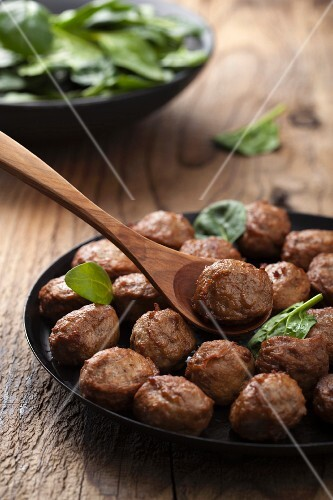 Meatballs in a frying pan and baby spinach