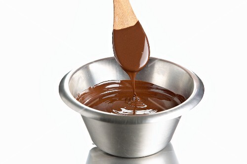 Melted chocolate in a bowl with a wooden spoon