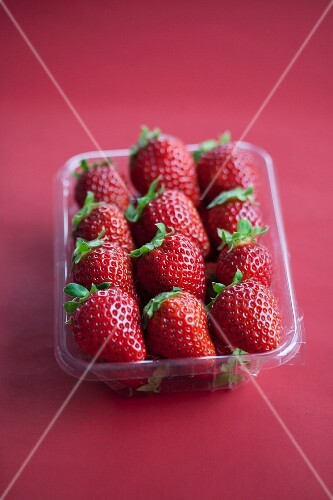 Fresh strawberries in a plastic punnet on a Bordeaux-red surface