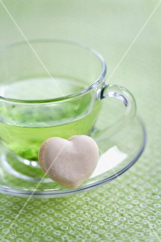 A heart-shaped vanilla macaroon with a cup of green tea