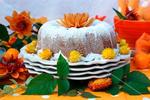 A Bundt cake coated with icing sugar and decorated with orange flowers