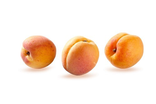 Three apricots against a white background