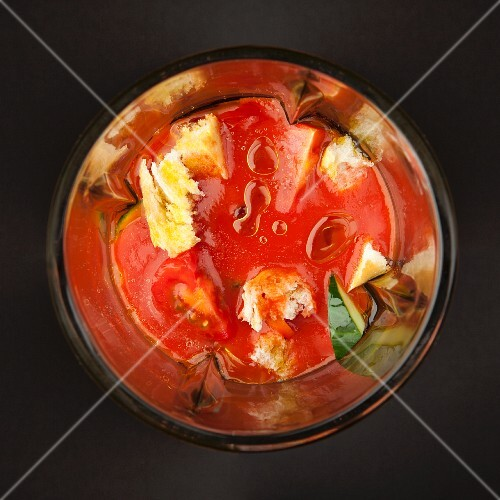 Mixed vegetables, tomato sauce and diced bread (for gazpacho) in a blender