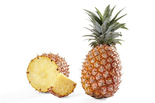 A whole pineapple and one sliced open