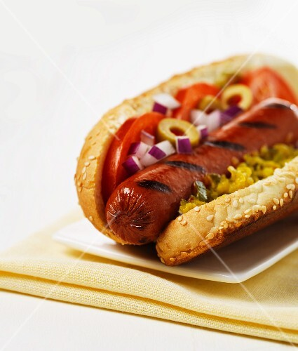 A hot dog with tomatoes, onions and relish