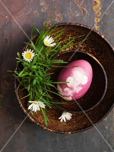 A pink decorated egg for Easter in a wooden bowl with daisies