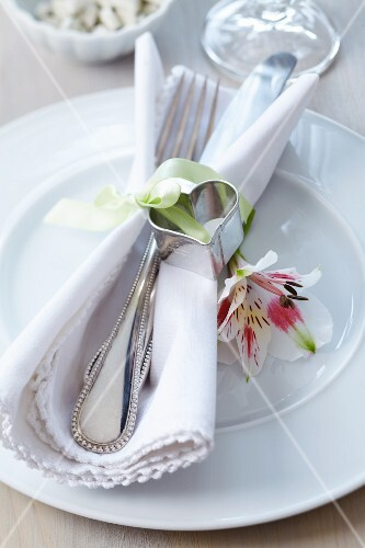 Heart-shaped pastry cutter as napkin ornament and lily on plate