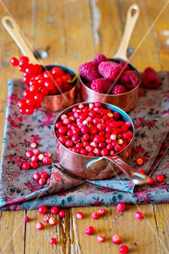 Assorted berries in copper saucepans