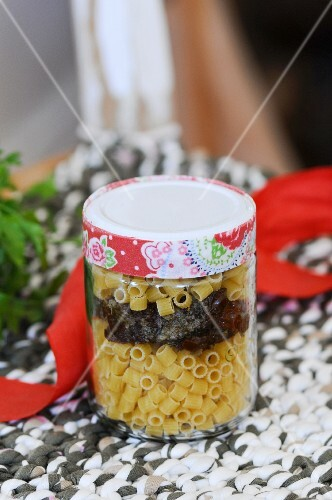 Raw macaroni in a jar with olive and tomato pesto