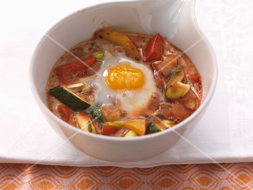 An egg cooked in the pot with vegetables