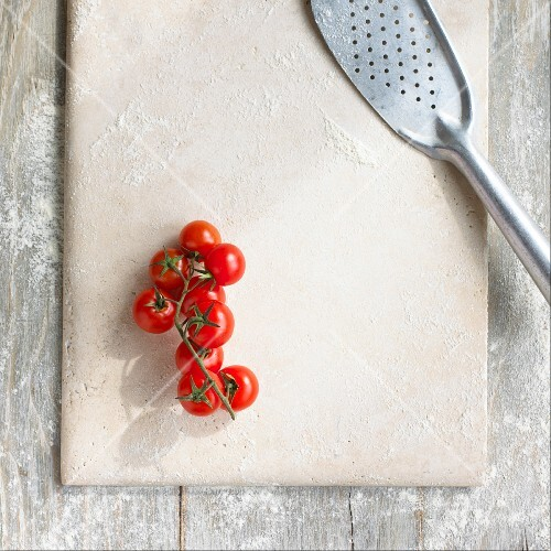 A floured stone slab with cherry tomatoes and a fish slice