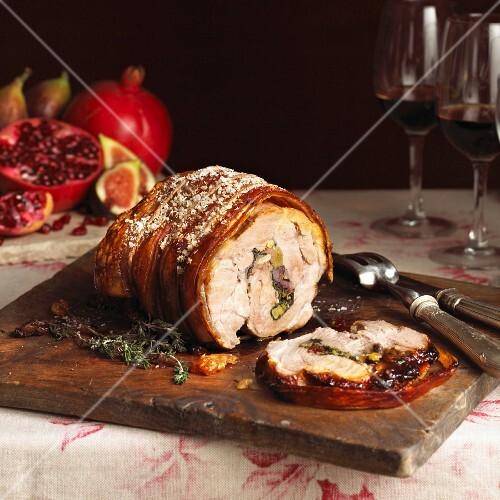 Rolled stuffed roast pork on a chopping board, partly sliced