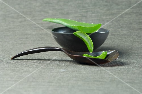 Sliced aloe vera shoots with a bowl and a wooden spoon