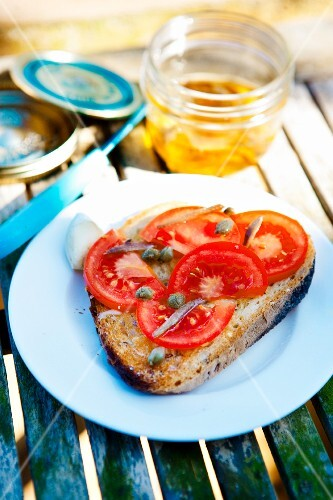 A slice of bread topped with tomatoes, capers and anchovies