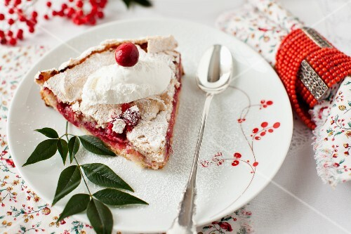 A Slice of Cranberry Meringue Tart on a Plate; Dusted with Powdered Sugar
