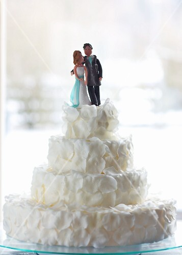 An original wedding cake decorated with white rose petals and a bridal couple in marzipan