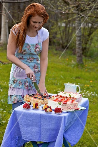 A young woman cutting a layer cake