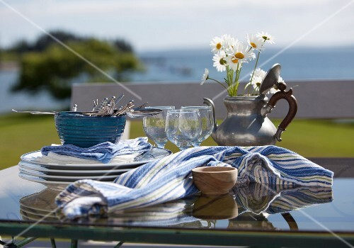Plates and Glasses on an Outdoor Table to be Set