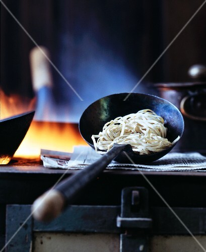 Oriental egg noodles in a ladle on a stove