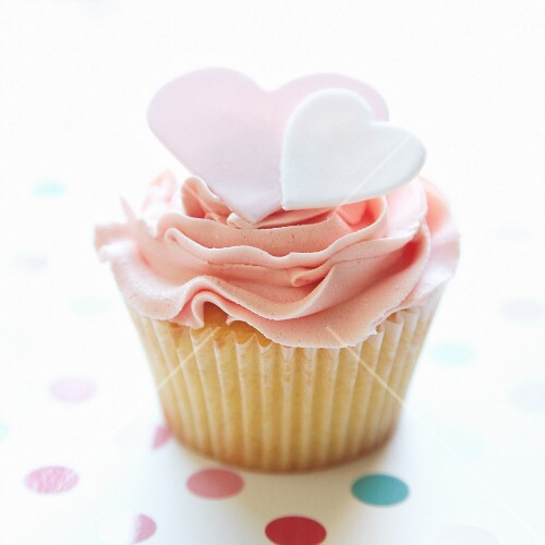 A cupcake decorated with sugar hearts