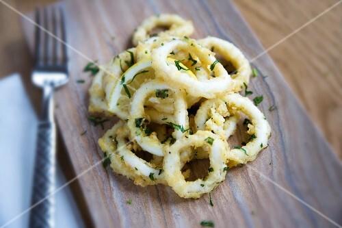 Squid rings in seasoned flour with parsley and lemon