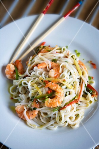Plated stir-fried noodles with tiger prawns, chilli, ginger, sesame oil and coriander