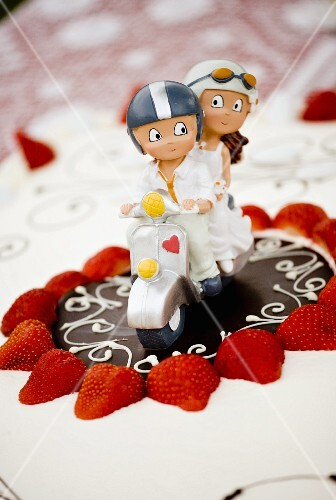 A decorative bridal couple on a wedding cake