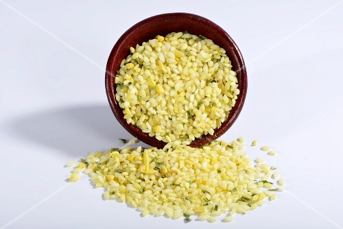 Vialone Nano risotto rice with almonds, lemon oil, turmeric and chives with a ceramic dish